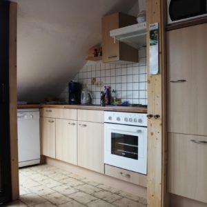 Wohnraum mit der Küche - die Küche ist komplett eingerichtet, vom Gefrierschrank über einen E-Herd mit Backofen bis zu Eierkocher; alles ist vorhanden
